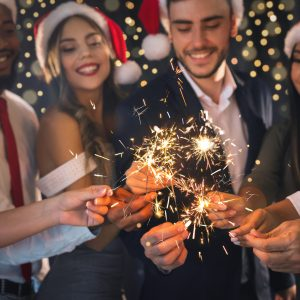 Merry Christmas greeting card. Group of happy friends in New Year eve with sparkling bengal lights, closeup